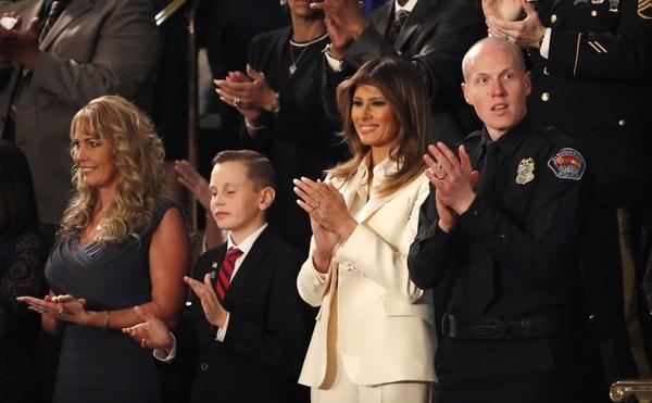 La primera dama, Melania Trump, asistió al primer discurso sobre el Estado de la Unión. En la foto la acompañan Preston Sharp,quien organizó la ubicación de banderas en las tumbas de 40.000 veteranos, yel oficialRyan Holets de la policía de Albuquerque (REUTERS/Leah Millis)